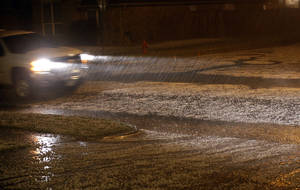 Photo - A car drives through hail on the residential street in Northwest Oklahoma City, Friday, April 26, 2013. Photo by Sarah Phipps, The Oklahoman <strong>SARAH PHIPPS - SARAH PHIPPS</strong>