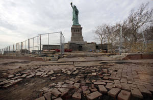 Photo - Parts of the brick walkway of Liberty Island that were damaged in Superstorm Sandy were shown during a tour, in New York,  Friday, Nov. 30, 2012. Tourists in New York will miss out for a while on one of the hallmarks of a visit to New York, seeing the Statue of Liberty up close. Though the statue itself survived Superstorm Sandy intact, damage to buildings and Liberty Island's power and heating systems means the island will remain closed for now, and authorities don't have an estimate on when it will reopen. (AP Photo/Richard Drew)