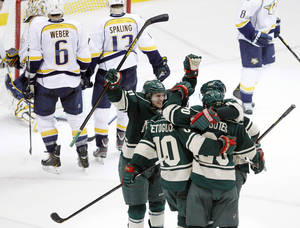 Photo - Minnesota Wild left wing Zach Parise (11) celebrates with teammates Devin Setoguchi (10), Ryan Suter (20) and Mikko Koivu, of Finland, after Setoguchi scored the game-winning goal against Nashville Predators goalie Chris Mason with assists by Suter and Koivu during overtime of an NHL hockey game Saturday, Feb. 9, 2013 in St. Paul, Minn. The Wild won 2-1. (AP Photo/Genevieve Ross)