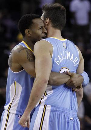 Photo -   Denver Nuggets' Andre Iguodala, left, embraces teammate Danilo Gallinari during double overtime in an NBA basketball game against the Golden State Warriors Saturday, Nov. 10, 2012, in Oakland, Calif. (AP Photo/Ben Margot)
