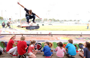 Photo - Tyler Thulin from Miami, OK, skates over a group of children painting the community's local skate park as part of the Oklahoma Arts Council's Leadership Arts program. PHOTO BY GARY CROW. <strong></strong>