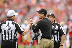 Photo - San Francisco 49ers head coach Jim Harbaugh, center, speaks with referee Scott Green, left, and head linesman Tom Stabile during the first half of an NFL football game against the Tampa Bay Buccaneers, Sunday, Dec. 15, 2013, in Tampa, Fla. (AP Photo/Brian Blanco)
