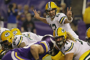 Photo - Green Bay Packers quarterback Aaron Rodgers (12) calls a play in the first half of an NFL football game against the Minnesota Vikings, Sunday, Oct. 27, 2013, in Minneapolis. (AP Photo/Ann Heisenfelt)