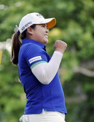 Photo - Inbee Park reacts after she pars the 18th hole to win the Wegmans LPGA golf championship in Pittsford, N.Y., Sunday, Aug. 17, 2014. Park successfully defended her title in the LPGA Championship, beating Brittany Lincicome with a par on the first hole of a playoff Sunday to end the United States' major streak at three. (AP Photo/Gary Wiepert)