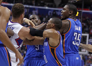 Photo - Los Angeles Clippers forward Blake Griffin, left, gets into a skirmish with Oklahoma City Thunder forward Serge Ibaka (9), forward Kevin Durant, right, and guard Russell Westbrook, second form right, in the first half of an NBA basketball game Wednesday, Nov. 13, 2013, in Los Angeles. Ibaka and Clippers forward Matt Barnes were ejected. (AP Photo/Alex Gallardo)