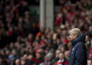 Photo - Arsenal's manager Arsene Wenger watches his team's English Premier League soccer match against Liverpool at Anfield Stadium, Liverpool, England, Saturday Feb. 8, 2014. (AP Photo/Jon Super)