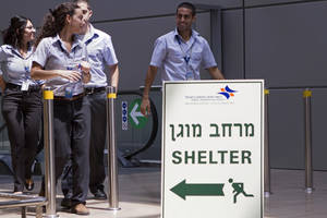 Photo - Israelis airport workers pass a sign pointing to a shelter for refuge in case a warning siren indicates the possibility of an incoming rocket, at Ben Gurion International airport a day after the U.S. Federal Aviation Administration imposed a 24-hour restriction on flights after a Hamas rocket landed within a mile of the airport, in Tel Aviv, Israel, Wednesday, July 23, 2014. U.S. Secretary of State John Kerry flew into Israel's main airport Wednesday despite a Federal Aviation Administration ban in an apparent sign of his determination to achieve a cease-fire agreement in the warring Gaza Strip despite little evidence of progress in ongoing negotiations. (AP Photo/Dan Balilty)