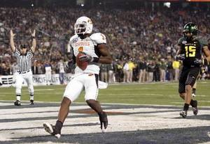 Photo - OSU's  Dez  Bryant scores a touchdown in front of Patrick Chung of Oregon during the Holiday Bowl college football game between Oklahoma State University and Oregon at Qualcomm Stadium in San Diego, Tuesday, Dec. 30, 2008. PHOTO BY BRYAN TERRY, THE OKLAHOMAN