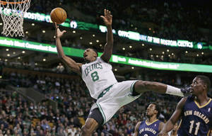 Photo - Boston Celtics forward Jeff Green (8) drives to the basket past New Orleans Pelicans guard Jrue Holiday (11) and forward Al-Farouq Aminu, rear, during the third quarter of an NBA basketball game, Friday, Jan. 3, 2014, in Boston. (AP Photo/Charles Krupa)
