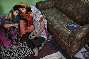 Photo -   Indian Lokinder Kaur, center, mourns with her daughters Jasbir Kaur, 24, left, and Jaspreet Kaur, 21, right, as a picture of her husband Ranjeet Singh, who was killed in the shooting attack at a Sikh temple in Wisconsin, at the family home in New Delhi, India, Tuesday, Aug. 7, 2012. Singh, one of killed in a shooting attack on the temple, never came home even once in 16 years, working at a grocery store during the week and volunteering at the Sikh gurdwara on weekends. He promised his family he was doing what had to be done to get a green card so they could come join him. (AP Photo/Kevin Frayer)
