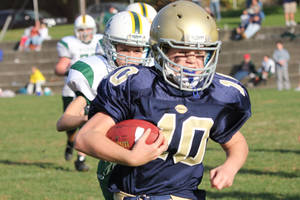 photo - In this 2012 photo provided by Marycecelia Pla, her daughter, Caroline Pla, foreground, carries the ball during a Catholic Youth Organization league football game. The 11-year-old girl who's been playing football since kindergarten wants Philadelphia's Roman Catholic archdiocese to overturn a boys-only rule. (AP Photo/Pla Family)