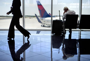 Photo - A passenger sits at right in the international terminal at Hartsfield-Jackson airport, Friday, April 26, 2013, in Atlanta. Congress easily approved legislation Friday ending furloughs of air traffic controllers that have delayed hundreds of flights daily, infuriating travelers and causing political headaches for lawmakers.(AP Photo/David Goldman) ORG XMIT: GADG102