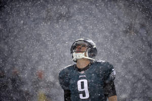 Photo - Philadelphia Eagles' Nick Foles warms up as snow falls before an NFL football game against the Detroit Lions, Sunday, Dec. 8, 2013, in Philadelphia. (AP Photo/Matt Rourke)
