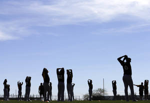 Photo - Oakland Athletics players stretch during spring training baseball practice Saturday, Feb. 15, 2014, in Scottsdale, Ariz.  (AP Photo/Gregory Bull)