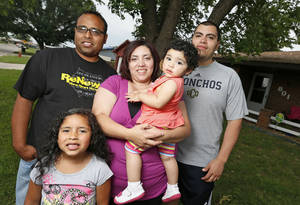 Photo - Kaylee Sanchez, 6, her father Eli Sanchez, mother Maria Sanchez, sister Ellie Sanchez, 1, and uncle Miguel Blanco pose for a photo in front of the Sanchez's home in the Plaza Towers housing addtion in Moore. Photo by Nate Billings, The Oklahoman  <strong>NATE BILLINGS - NATE BILLINGS</strong>