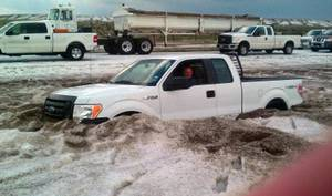 "Photo -   In this Wednesday, April 11, 2012 photo provided by the Amarillo/Potter/Randall Office of Emergency Management a motorist sits in a truck partially buried in slushy hail near Amarillo, Texas. Weather service crews are assessing the damage from a Texas Panhandle storm that dumped several feet of nickel-sized hail, stranded motorists in muddy, hail drifts and closed a highway for several hours. National Weather Service Meteorologist Justyn Jackson said Thursday that hail that fell amid a rainstorm the day before was real small but ""there was a lot of it"" in a concentrated area, accumulating 2- to 4-feet deep. (AP Photo/Courtesy of Amarillo/Potter/Randall Office of Emergency Management)"