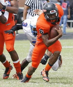 photo - Douglass' Shon Bridges outruns the tackle of Millwood's Josh Turner during the annual Soul Bowl between Millwood at Douglass in 2010. <strong>PAUL HELLSTERN - THE OKLAHOMAN</strong>