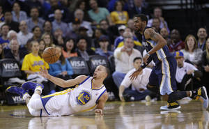 Photo - Golden State Warriors guard Stephen Curry, left, reaches for the ball as he falls down, while Memphis Grizzlies guard Mike Conley, right, watches during the first half of an NBA basketball game Friday, March 28, 2014, in Oakland, Calif. (AP Photo/Marcio Jose Sanchez)