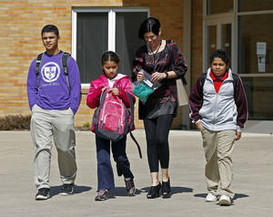 Photo -   FILE - In this March 16, 2011 file photo, Heather Coffy, right center, leaves the St. Monica School with her children, left to right, Delano Coffy, 15, Alanna Marshall, 8, and Darius Coffy, 11, in Indianapolis. Students like Delano are at the heart of brewing political fights and court battles over whether public dollars should go to school vouchers to help make private schools more affordable. (AP Photo/Michael Conroy, File)