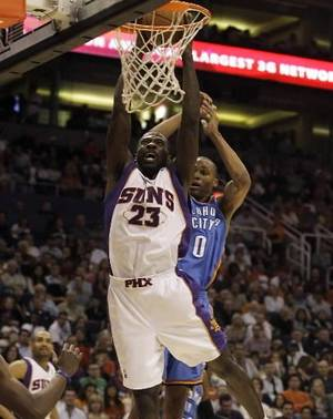 Photo - Phoenix Suns guard Jason Richardson dunks the ball in front of Oklahoma City Thunder guard Russell  Westbrook, right, in the second quarter of an NBA basketball game Friday, Feb 20, 2009, in Phoenix. (AP Photo/Paul Connors)