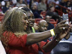 Photo - Tennis player Serena Williams, left, poses for a photo with a fan during an NBA basketball game between the Miami Heat and Utah Jazz, Monday, Dec. 16, 2013, in Miami. The Heat defeated the Jazz 117-94. (AP Photo/Lynne Sladky)
