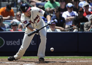 Photo - Atlanta Braves' Alex Wood bunts against the San Francisco Giants and advances to first base on a throwing error during the third inning of a baseball game on Sunday, May 4, 2014, in Atlanta. (AP Photo/David Tulis)