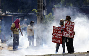 "Photo - Masked protesters stand amid tear gas holding signs a few miles from the soccer stadium where Spain and Italy will play in a Confederations Cup semifinal soccer game in Fortaleza, Brazil, Thursday, June 27, 2013. Their signs read in Portuguese ""Police, I'm here for your family,"" right, and ""Your violence is repulsive. Wake-up!""  It's the latest in a series of massive, nationwide protests that have hit Brazil since June 17. Demonstrators are angered about corruption and poor public services despite a heavy tax burden. Protests are also denouncing the billions of dollars spent to host the World Cup and the 2016 Olympics in Rio - money they say should be going toward better hospitals, schools, transportation projects and schools. (AP Photo/Natacha Pisarenko)"