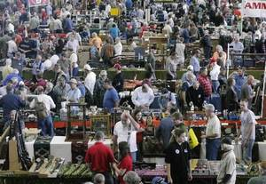 photo - Visitors walk around gun and ammunition vendor's displays at the Wanenmacher's Tulsa Arms Show in Tulsa, Okla. on November 10, 2012. JAMES GIBBARD/Tulsa World