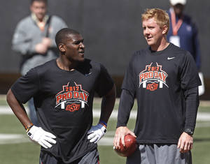 Photo - Brandon Weeden, right, and Justin Blackmon talk during Oklahoma State's Pro Day on Friday in  Stillwater. AP PHOTO