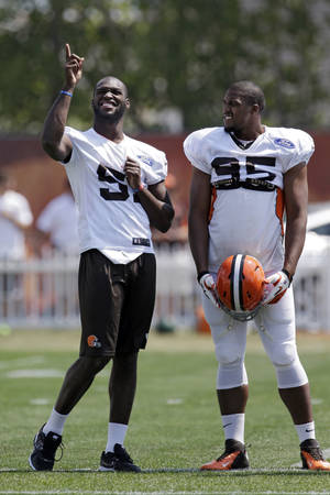Photo - Cleveland Browns linebacker Barkevious Mingo, left, talks with defensive end Armonty Bryant during practice at the team's NFL football training facility in Berea, Ohio Wednesday, Aug. 21, 2013. Mingo sat out practice with a bruised lung. (AP Photo/Mark Duncan)