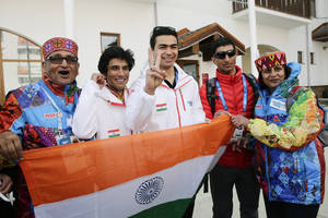 Photo - Indian athletes, alpine skier Thakur Himanshu, second left, luger Shiva Keshavan, center, and cross-country skier Nadeem Iqbal, second right, pause for photos after a welcome ceremony for the Indian Olympic team at the Mountain Olympic Village during the 2014 Winter Olympics, Sunday, Feb. 16, 2014, in Krasnaya Polyana, Russia. (AP Photo/Jae C. Hong)