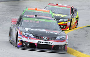 Photo - Sprint Cup driver Denny Hamlin (11) leads Danica Patrick and Clint Bowyer through turn four during the first round of practice for a NASCAR auto race at Martinsville Speedway in Martinsville, Va., Friday March 28, 2014. (AP Photo/Mike McCarn)