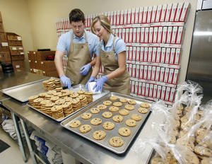 Photo - Mac and Heather Carver prepare packages of cookies at Cookie Advantage in Edmond. Photos by PAUL HELLSTERN, The Oklahoman