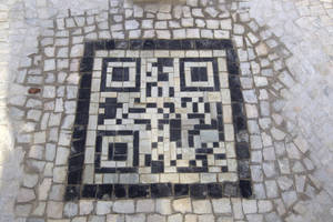 photo - A two-dimensional bar code, or QR code, as they're known, made from black and white stones covers a sidewalk near the beach in Rio de Janeiro, Brazil, Friday, Jan. 25, 2013. The QR codes are being placed at tourist spots which can be scanned with a mobile device for information about the site. (AP Photo/Silvia Izquierdo)