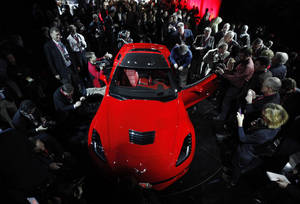 photo - Journalists surround General Motors new 2014 Chevrolet Corvette Stingray, Sunday, Jan. 13, 2013, the night before press days at the North American International Auto Show in Detroit. When 1,000 GM engineers and designers started work on the next-generation Corvette, they began with the usual priority list for a muscle car. Killer looks. Big engine. Fast. But topping the list was something that belies the roar of the Chevrolet's giant V-8: Gas mileage. (AP Photo/Paul Sancya)
