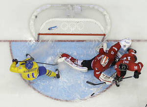 Photo - Sweden forward Daniel Alfredsson (11) scores a goal against Switzerland goaltender Reto Berra in the third period of a men's ice hockey game at the 2014 Winter Olympics, Friday, Feb. 14, 2014, in Sochi, Russia. Sweden won 1-0.(AP Photo/Mark Humphrey)