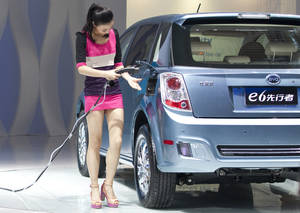 photo -   A woman demonstrates BYD's new charging and discharging technology on a BYD e6 electric car during the 2012 Beijing International Automotive Exhibition in Beijing, China, Monday, April 23, 2012. (AP Photo/Alexander F. Yuan)