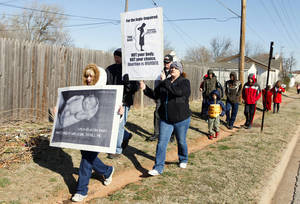 Photo - Angela Jeffers of Moore and Stephanie Tarlton of Oklahoma City carry signs as they walk down Western Avenue Monday while participating in the 2013 March for Life OKC from Our Lady's Cathedral, 3214 N Lake Ave., to the state Capitol building. <strong>PAUL B. SOUTHERLAND - PAUL B. SOUTHERLAND</strong>