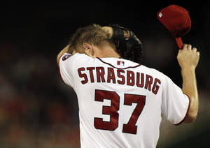 Photo -   Washington Nationals starting pitcher Stephen Strasburg wipes his face on the mound during the second inning of a baseball game against the Miami Marlins at Nationals Park, Friday, Sept. 7, 2012, in Washington. (AP Photo/Alex Brandon)