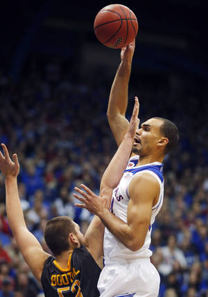 Photo - Kansas forward Perry Ellis, right, shoots while covered by Toledo center Nathan Boothe during the first half of an NCAA college basketball game in Lawrence, Kan., Monday, Dec. 30, 2013. (AP Photo/Orlin Wagner)