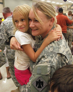 Photo - Staff Sgt. Sarah Scott, of Noble, hugs her daughter Anna, 8, as she and fellow soldiers from the 1-245th Airfield Operations Battalion return home Tuesday in Norman after spending eight months in Afghanistan. PHOTO BY STEVE SISNEY, THE OKLAHOMAN