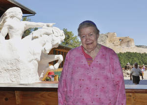 Photo - FILE - In this Aug. 21, 2010 file photo, Ruth Ziolkowski, president and chief executive of the Crazy Horse Memorial, stands in front of a plaster rendering of Crazy Horse with what will be the world's largest mountain carving in the background, near Custer, S.D. Ziolkowski is the widow of sculptor Korczak Ziolkowski, who started the memorial on June 3, 1948. Ruth, who took over the dream of her husband, upon his death in 1982 and turned it into a multimillion-dollar operation that draws more than a million visitors a year, died Wednesday May 21, 2014 at age 87 acording to a spokesman. (AP Photo/Dirk Lammers, File)