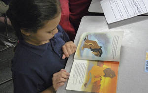 "Photo - Mark Twain Elementary second-grader Cienna Johnson, 8, reads ""The Lion King"" while waiting for her classmates to finish work. Oklahoma Watch photo.    <strong></strong>"