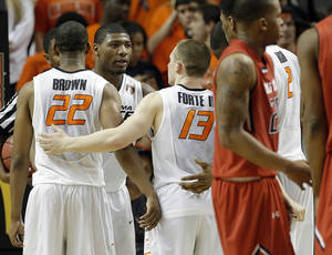 Photo - Oklahoma State's Marcus Smart (33) huddles with teammates after a foul during the men's college basketball game between Oklahoma State and Texas Tech at Gallagher-Iba Arena in Stillwater, Okla., Saturday, Feb. 22, 2014. OSU won 84-62. 
