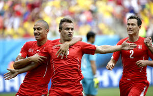 Photo - Switzerland's Xherdan Shaqiri, center, celebrates with teammate  Goekhan Inler, left, and Stephan Lichtsteiner (2) after scoring during the group E World Cup soccer match between Honduras and Switzerland at the Arena da Amazonia in Manaus, Brazil, Wednesday, June 25, 2014. (AP Photo/Felipe Dana)