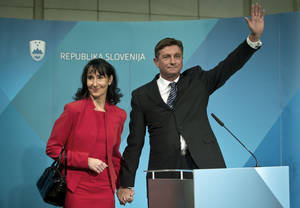 photo - President elect, Slovenia's former prime minister Borut Pahor, right, with his spouse Tanja Pecar waves to the media in Ljubljana, Slovenia, Sunday, Dec. 2, 2012.  Pahor, who has called for unity in the tiny EU nation amid growing discontent with government tax hikes and spending cuts, won the presidential election. (AP Photo/Darko Bandic)
