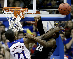 Photo - Kansas' Joel Embiid (21) blocks a shot by Georgetown's Aaron Bowen (23) during the first half of an NCAA college basketball game Saturday, Dec. 21, 2013, in Lawrence, Kan. (AP Photo/Charlie Riedel)