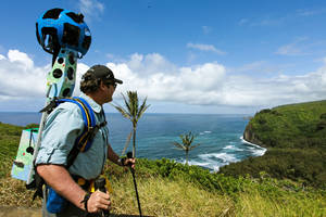 Photo - In this undated photo provided by Google, Rob Pacheco, president of Hawaii Forest & Trail, takes in the view at Pololu Valley's Awini Trail near Kapaau, Hawaii, while wearing the Street View Trekker. Hawaii's volcanoes, rainforests and beaches will soon be visible on Google Street View. The Mountain View, Calif., company said Thursday June 27, 2013  it was lending its backpack cameras to a Hawaii trail guide company to capture panoramic images of Big Island hiking trails. (AP Photo/Google)