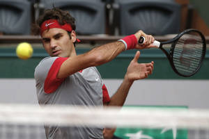 Photo - Switzerland's Roger Federer returns the ball during the third round match of the French Open tennis tournament against Russia's Dmitry Tursunov at the Roland Garros stadium, in Paris, France, Friday, May 30, 2014.  (AP Photo/Michel Euler)