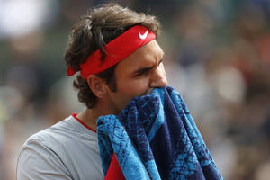 Photo - Switzerland's Roger Federer wipes his face during the first round match of the French Open tennis tournament against Slovakia's Lukas Lacko at the Roland Garros stadium, in Paris, France, Sunday, May 25, 2014. (AP Photo/Darko Vojinovic)